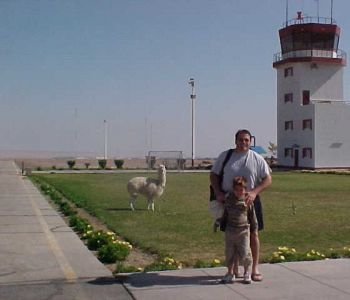 P. Michael Gandolfo IV & P. Michael Gandolfo III posing with a llama at the Tacna airport